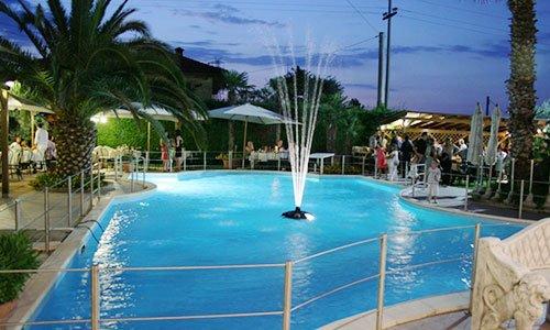 una piscina con una fontana in mezzo, delle palme, degli ombrelloni e delle persone