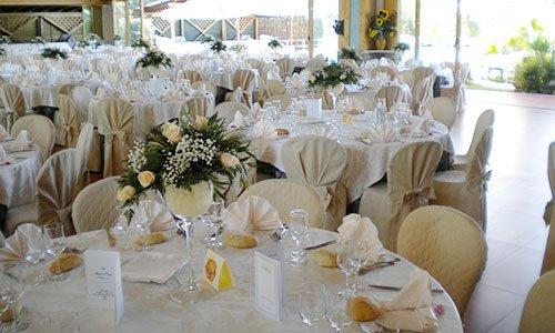 sala da pranzo con tavoli apparecchiati con una tovaglia bianca, sedie rivestite con una stoffa gialla, posate e calici e dei fiori bianchi al centro