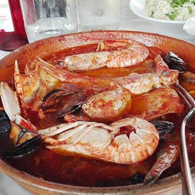 un piatto a base di crostacei e cozze  al sugo in una pentola marrone