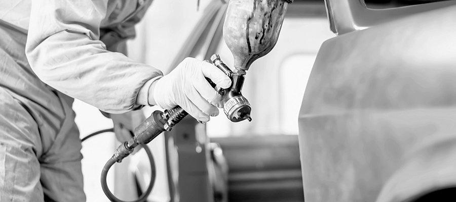 meccanico mentre effettua una verniciatura a una carrozzeria di un auto