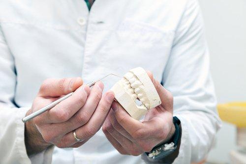 dentista con un calco di dentiera in mano