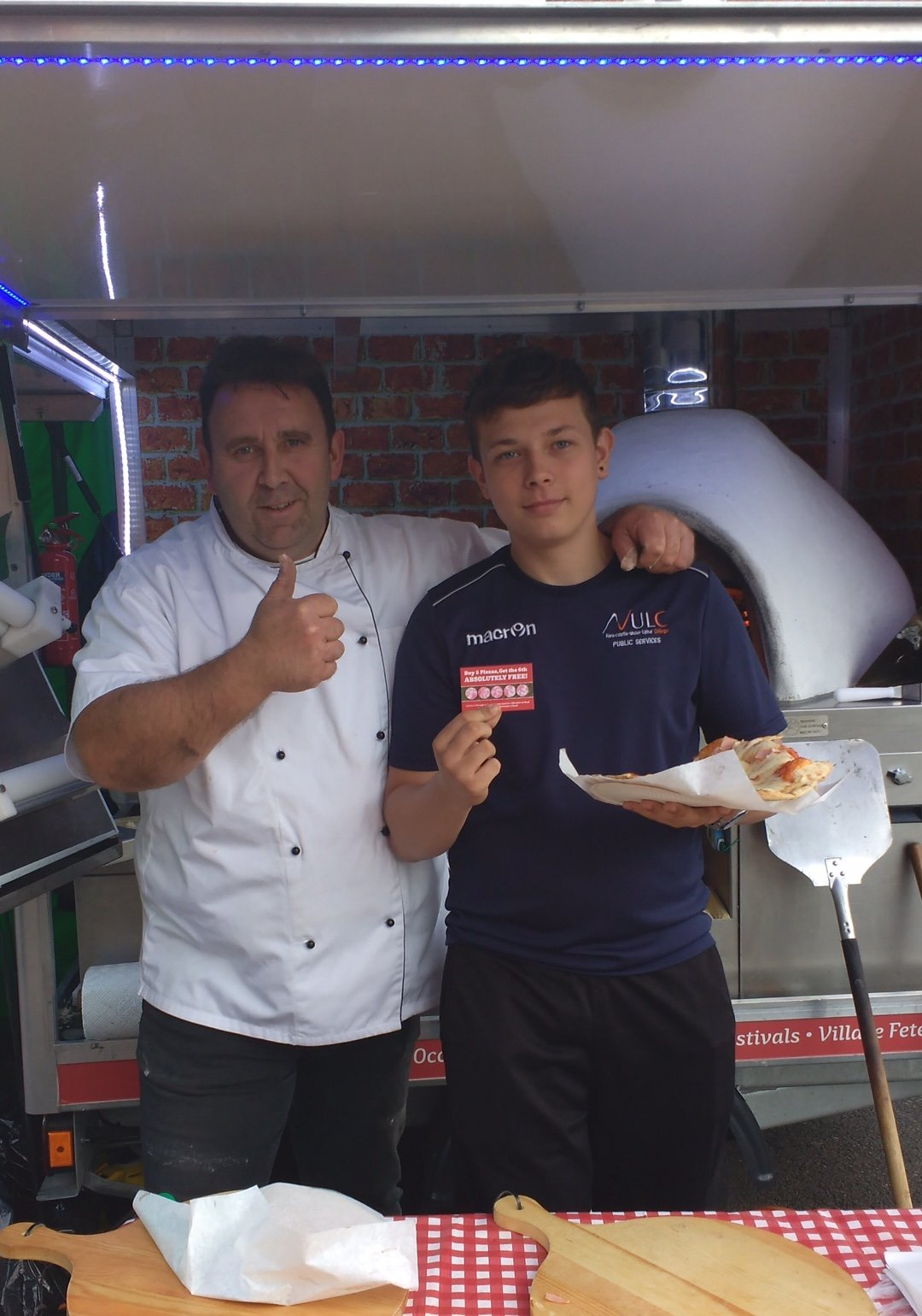 two pizzaiolo in front of a pizza oven