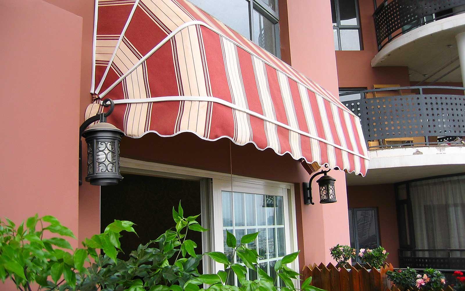 una veranda con una tenda di color rosso e color avorio