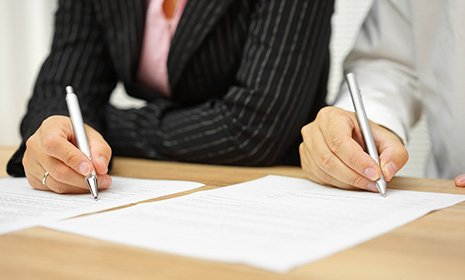 Woman and man signing on divorce papers