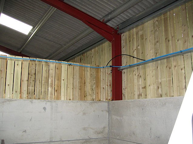 blue pipe fitted on the wooden wall