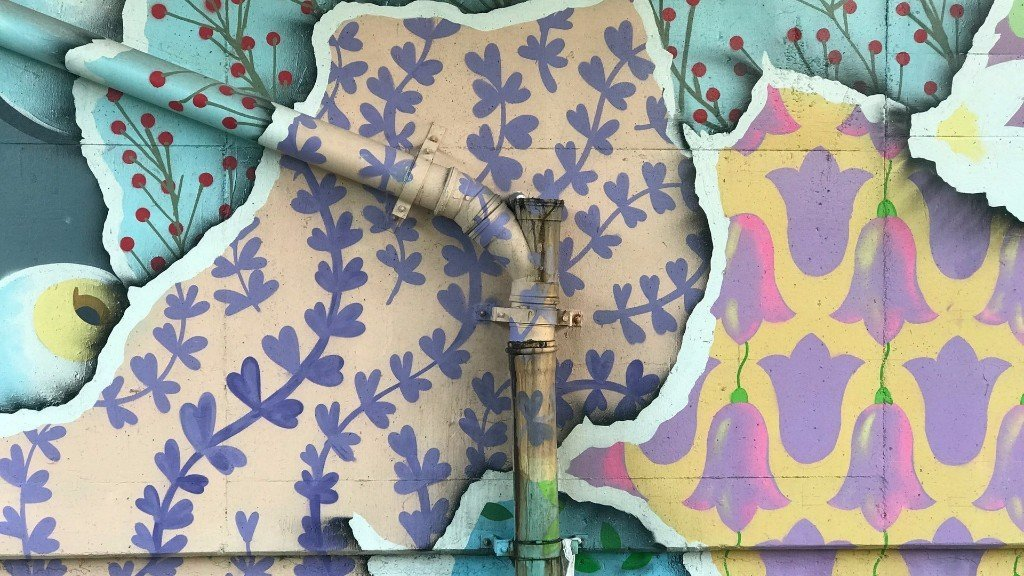 Spray painted wall paper textures on outside wall with pipe