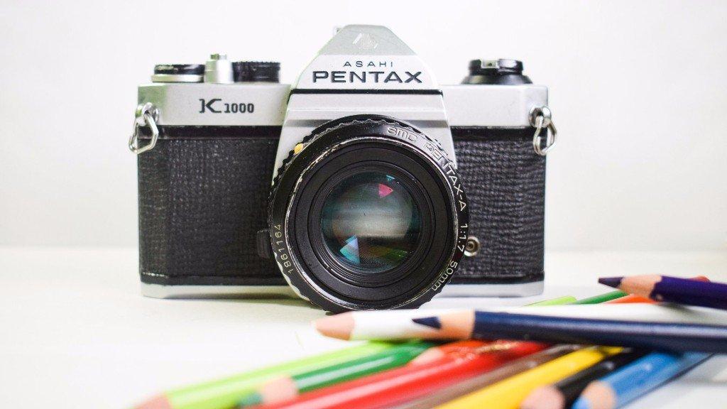 Vintage camera sitting behind colored pencils