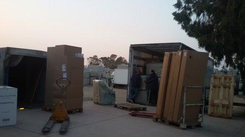 operai mentre sistemano dei bancali dentro il baule di un furgone