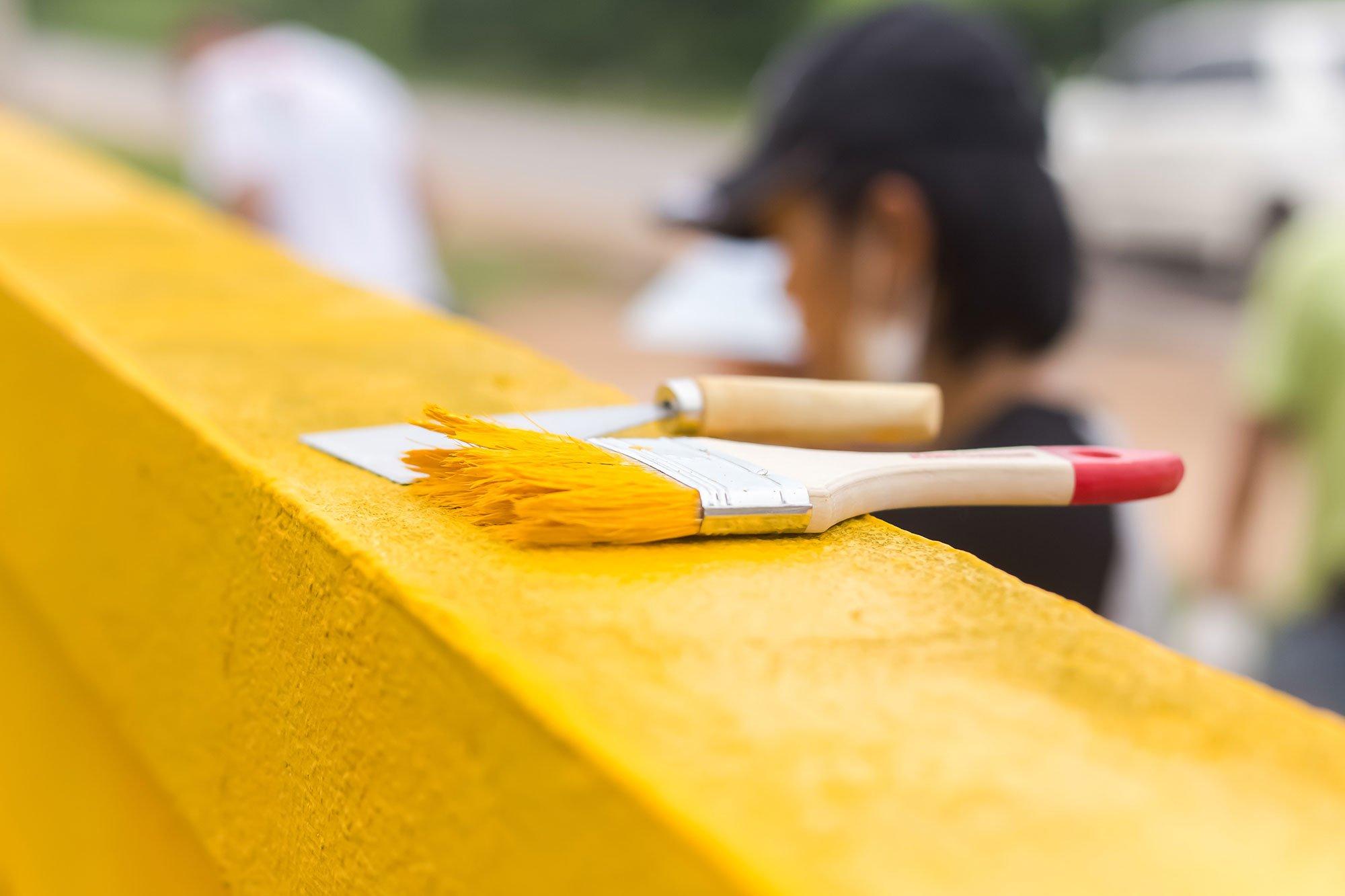 Legno di un balcone colorato di giallo con i pennelli
