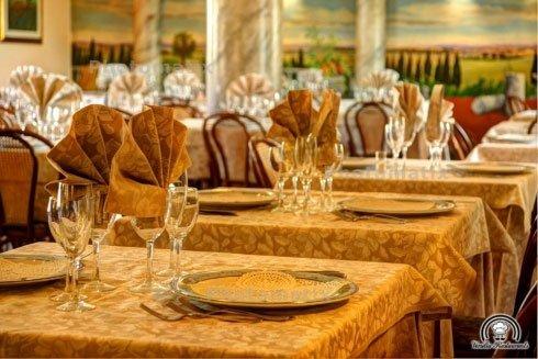 Dei tavoli apparecchiati con delle tovaglie di color beige, dei piatti e bicchieri