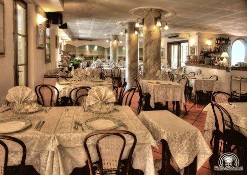 Dei tavoli apparecchiati e dei luci accesi all'interno di un ristorante
