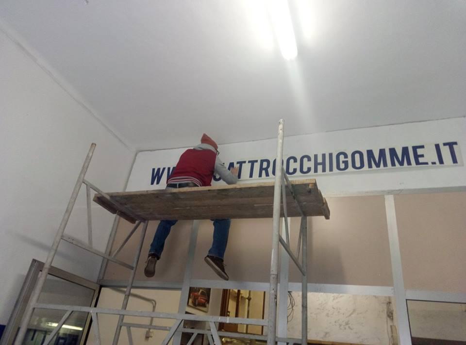 operaio installa striscione promozionale