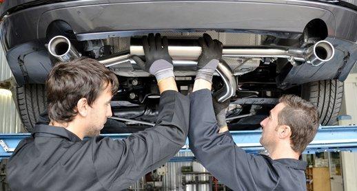 Technicians Installing Exhaust Muffler