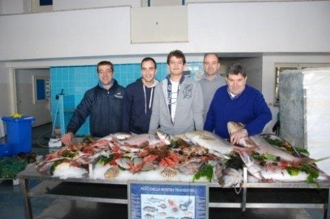 Del personale davanti a  un bancone con del pesce fresco