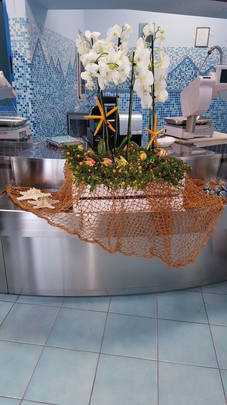 una composizione con una rete da pesca, conchiglie e orchidee