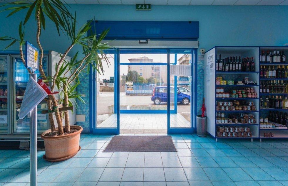 Una porta d'entrata e sulla destra uno scaffale con dei vasetti