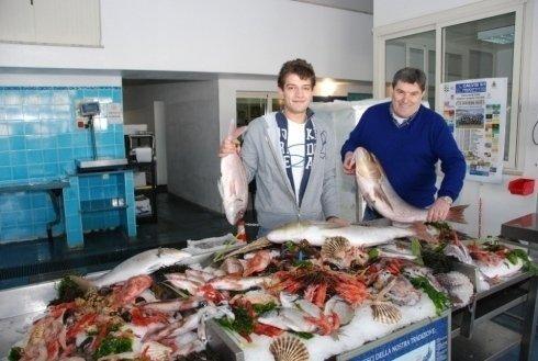 Due uomini con dei pesci in mano all'interno di una pescheria