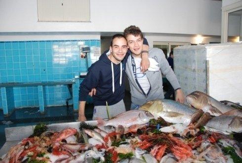 Due uomini abbracciati davanti a un bancone con del pesce fresco