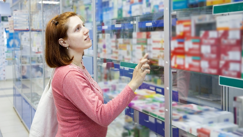 Woman looking through glass at prescriptions