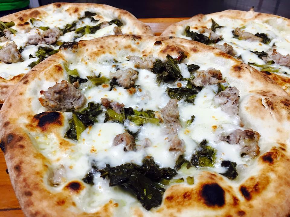 una pizza con salsiccia e broccoletti