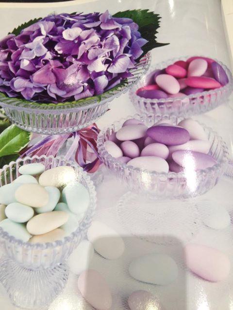 un vaso di color bianco e accanto delle  confezioni di confetti