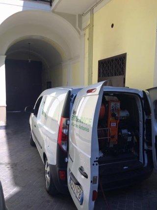 furgone della ditta NEW ECO SERVICE con dei macchinari all`interno del baule aperto