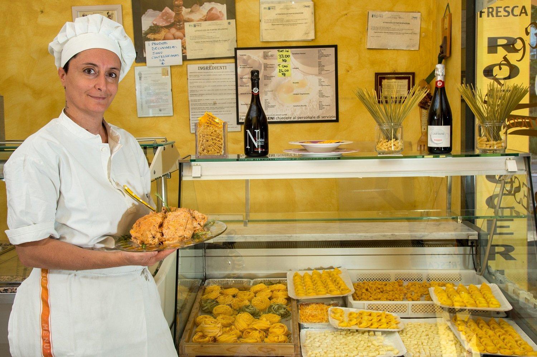 Una cuoca sorridente con un piatto di carne davanti a un bancone di pasta fresca