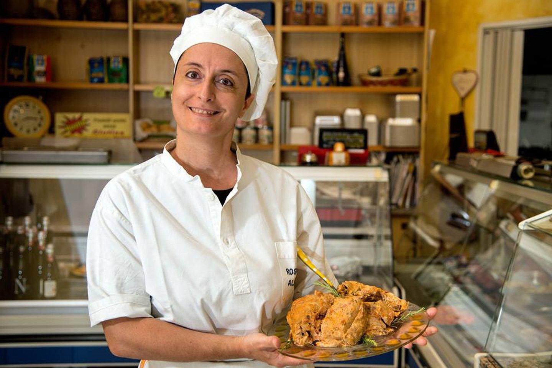 Una cuoca sorridente mostra un piatto di carne