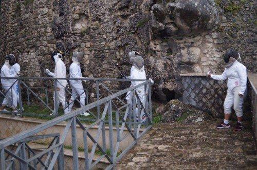 degli schermidori vicino a un muro di roccia