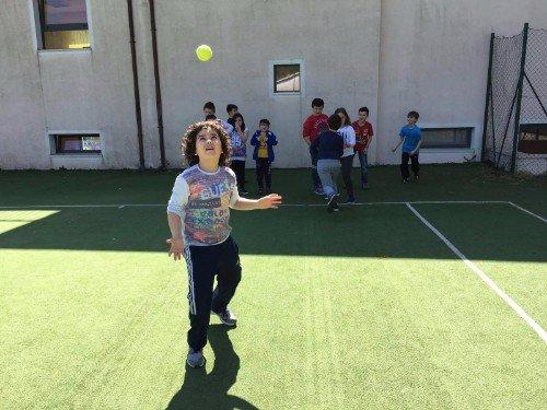 un bambino che sta ricevendo una pallina da tennis