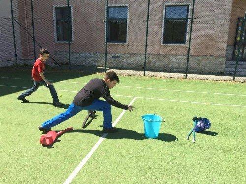 un bambino chinato a terra in un campo da tennis e vicino un secchio