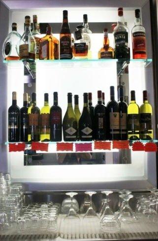 delle bottiglie di liquori su delle mensole e dei bicchieri