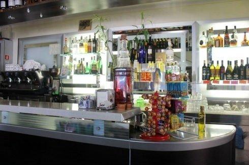 un bancone di un bar e dietro delle bottiglie di liquore e la macchina del caffè