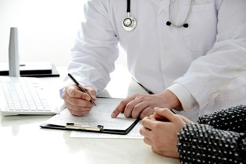 Doctor writing medical record and explaining for patient