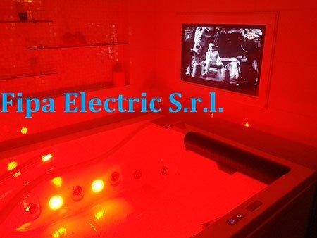 una vasca illuminata di rosso e una tv vicino