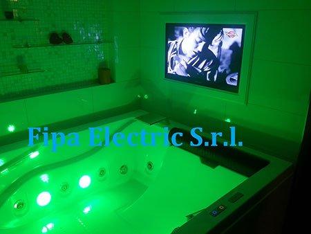 una vasca illuminata di verde e una tv vicino