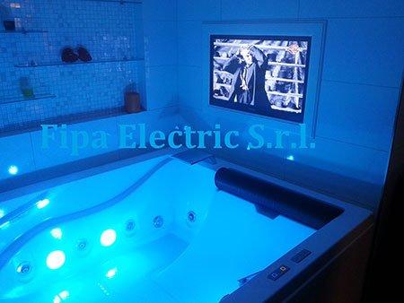 una vasca illuminata di blu e una tv vicino