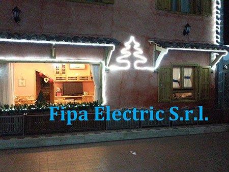una casa illuminata con un albero di Natale sulla facciata