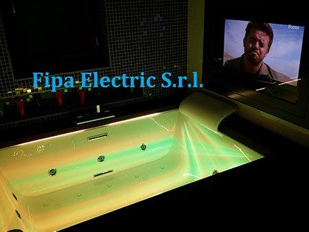 una vasca e accanto una tv accesa