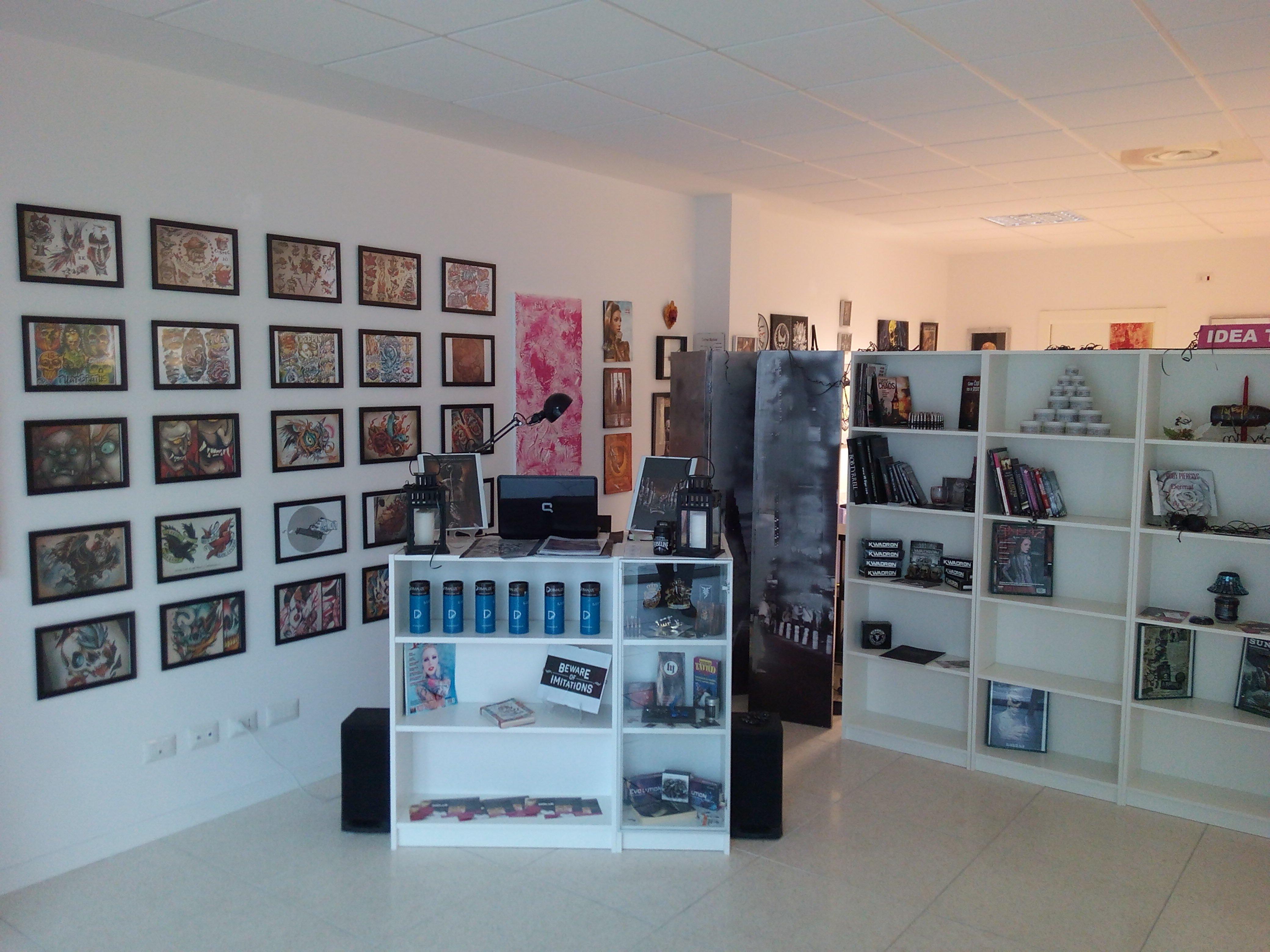 interno del negozio con una scrivania vetrina bianca con sopra un monitor, sulla sinistra dei quadretti appesi al muro che raffigurano degli esempi di tatuaggi e sulla destra uno scaffale con degli oggetti