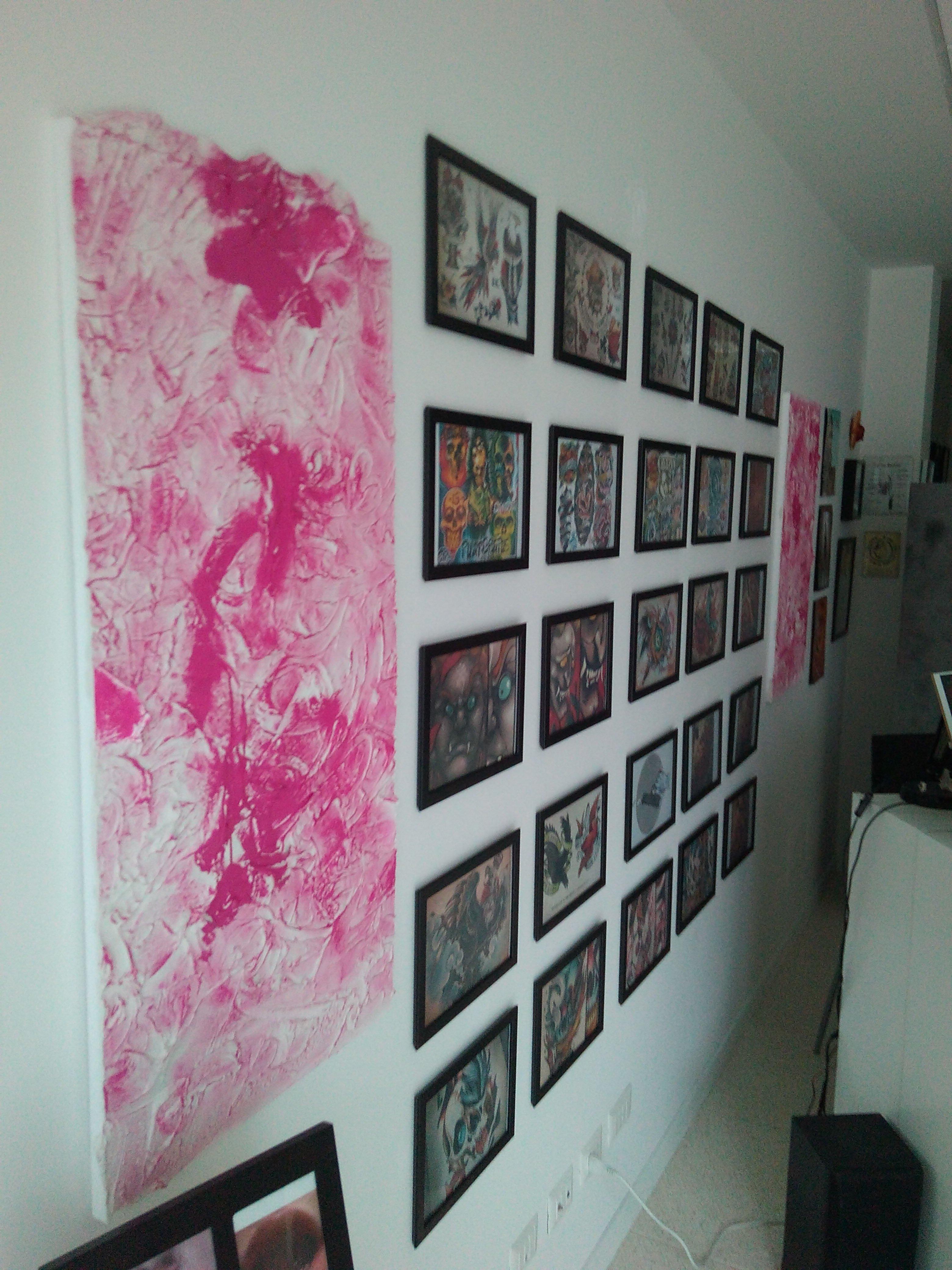 una parete con disegni floreali di color fucsia e dei quadri appesi raffiguranti dei modelli di tatuaggi