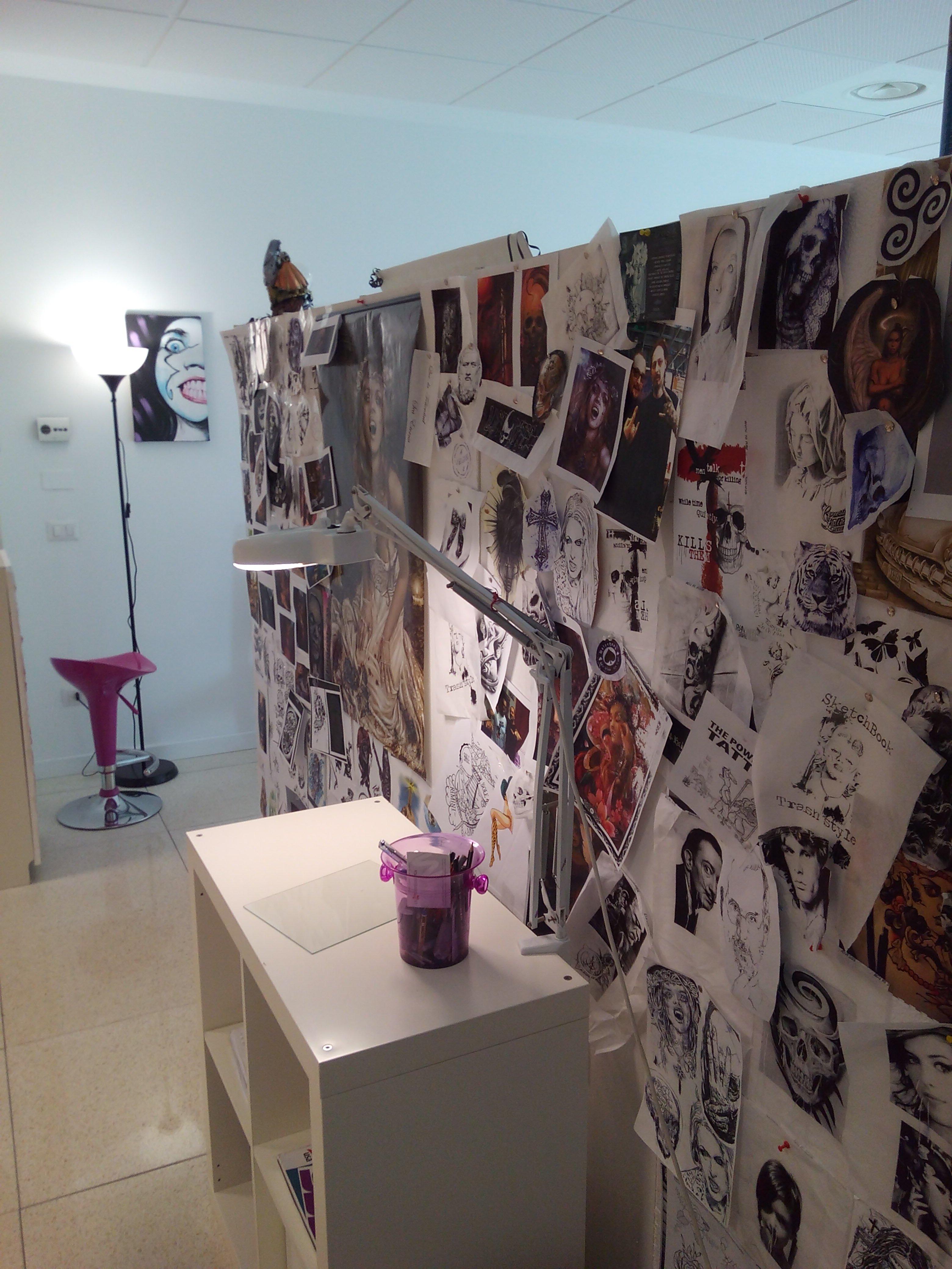 vista di alcune bozze di tatuaggi su fogli appesi a un pannello, davanti un piccolo tavolino con una lampada e in fondo uno sgabello fucsia