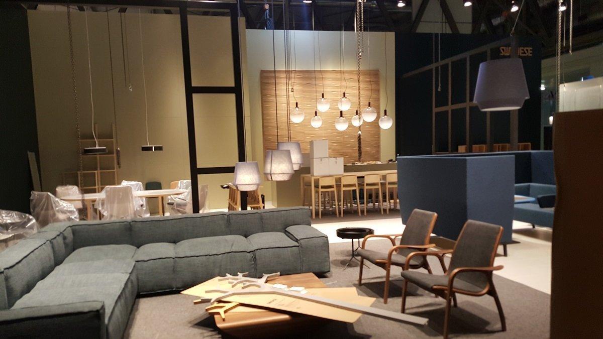 Grande sofá grigio, mobili di legno e lampade bianche