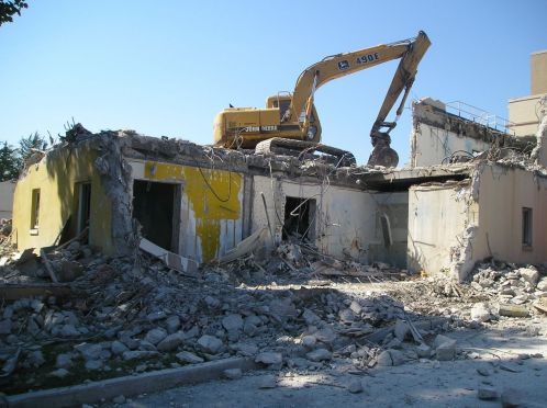 Backhoe tractor breaking up a concrete building in Omaha.