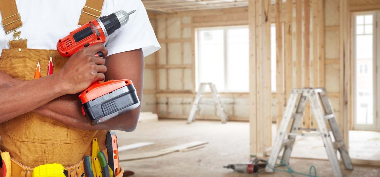 Operaio all'interno di una casa in costruzione sostenendo un cacciavite elettrico