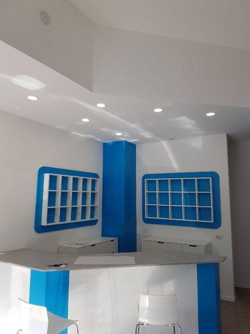 Banco di ricezione bianco, focolai alogeni sul tetto e casellario in blu al pari della colonna