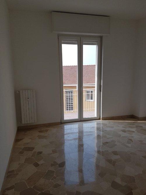 Camera con il nuovo suolo di marmo frammentato,radiatore e porta finestra di PVC