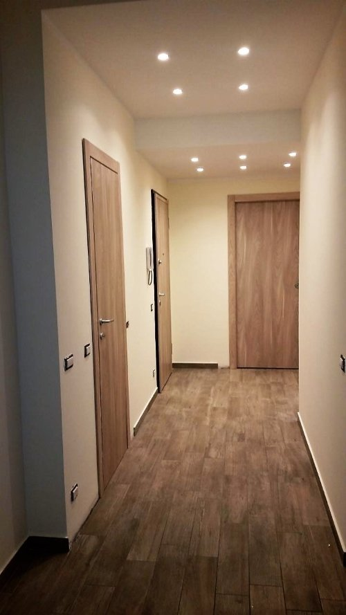 Corridoio di abitazione in legno, porte anche in legno e installazione halogena nel tetto