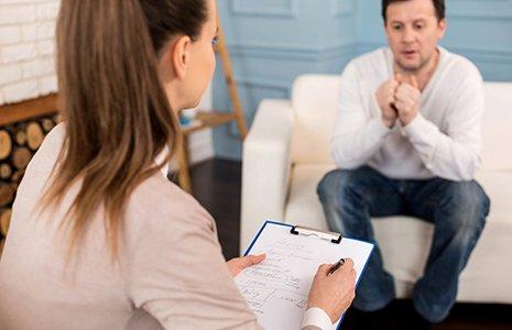 Un uomo giovane e preoccupato parla con la sua terapeuta