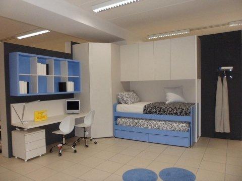 camera con dettaglio azzurri, letto singolo con un letto estraibile e scrivania con sedie